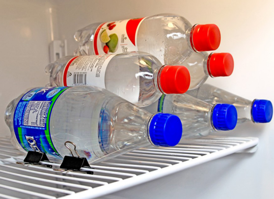 Use binder clips to keep bottles from rolling in fridge