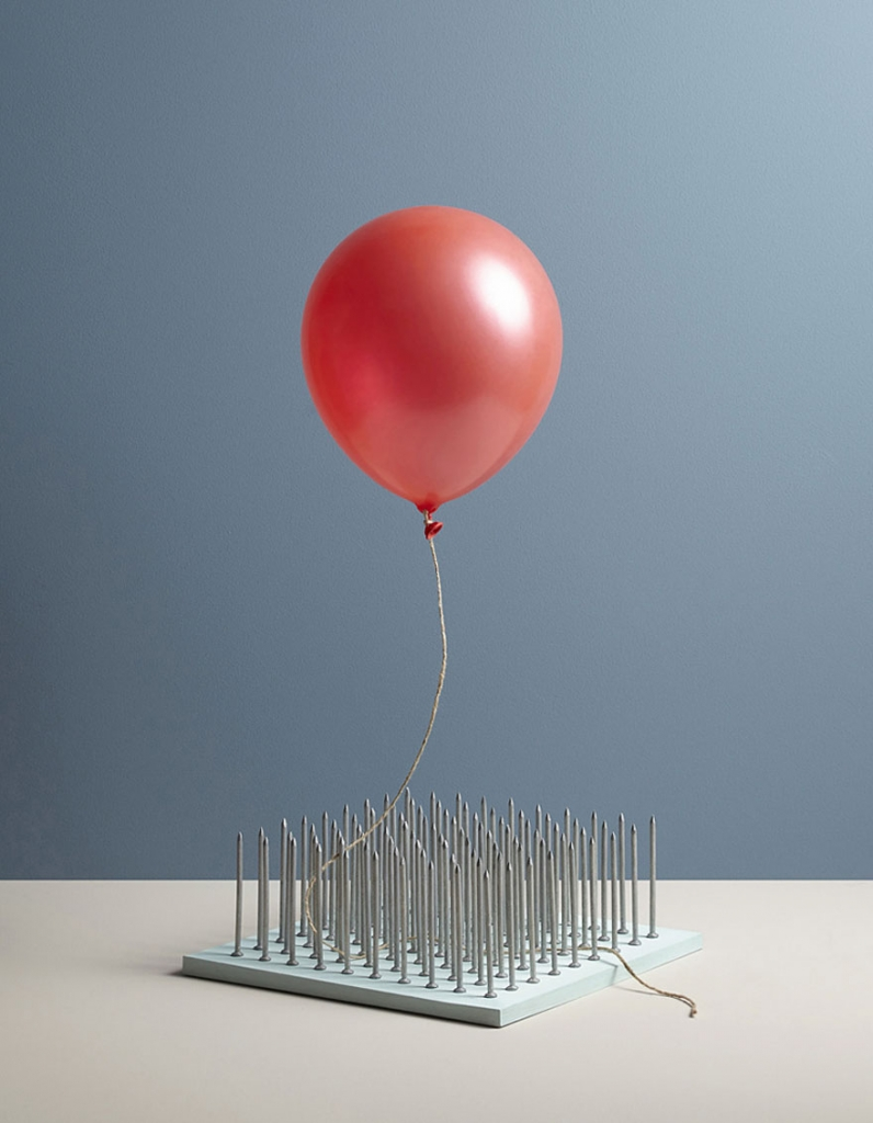 A balloon awaiting  a slow death above a plinth of pins|In Anxious Anticipation Aaron Tilley